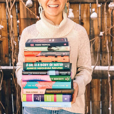 Sara Hildreth of FictionMatters holds books and wears a cozy sweater