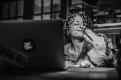Hannah Ellaham - BYOBrand Podcast Host Smiling At Her Dog Yara The Husky while sitting in from of laptop