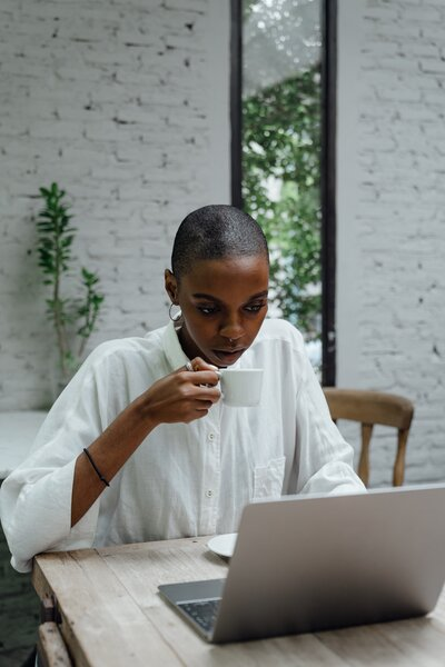 serious-black-businesswoman-using-laptop-while-sitting-in-4350216