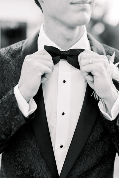 Groom grabbing his bowtie