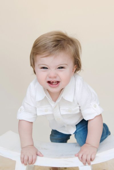 toddler boy kneeling on stool making a funny face
