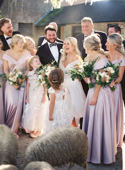 Mauve bridesmaid dresses and black groomsmen suits for a bridal party photo by the stableyards