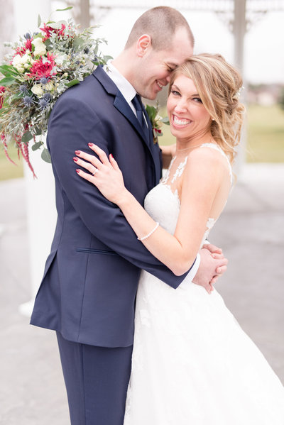 Bride laughs towards camera while groom snuggles to her.