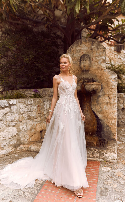 Inspired by the elements of nature's botannics, Halani is the a vision of romantic softness. Featuring layers of soft tulle, her gentle ballgown skirt features a diverse blend of floral embroidered lace appliques hiding amongst the layers. Her lace designs are highlighted with a scatter of delicate sequin embellishments, adding a light shimmer to her softness. Beautifully cut to flatter the body, Halani's V neck illusion straps are mirrored on the back of her gown in her deep V zipper back. Halani is the bridal gown that compliments an array of nuptial occasions and brides – from romantic to traditional to boho.