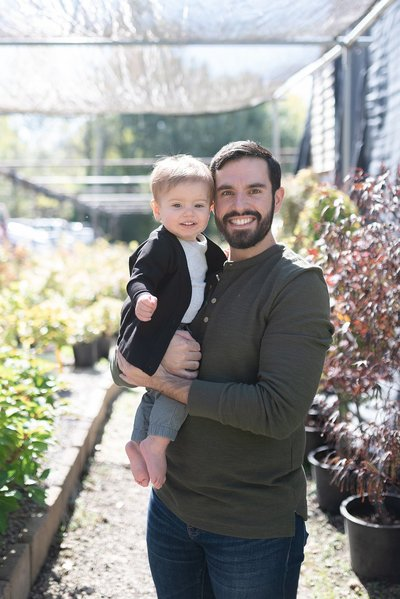 a father is holding his one year old son close to him for family portraits in franklin tennessee with Dolly deLong Photography