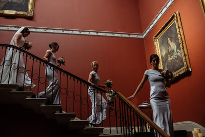 006-bride-with-bridesmaids-on-stairs-at-rise-hall--stately-home-wedding-photographer