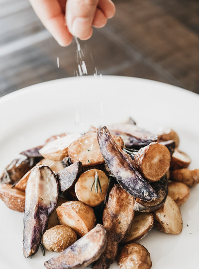 Photo of a plate of rosemary potatoes being seasoned by the fingers of the chef. Salt is sprinkled on top and the grains are blurry with motion. The potatoes are on a white plate and wooden table and look delicious.
