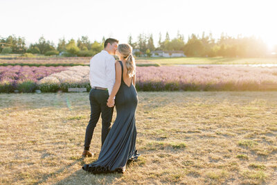 A photograph from behind as engaged couple kiss in a lavender field wearing cocktail attire