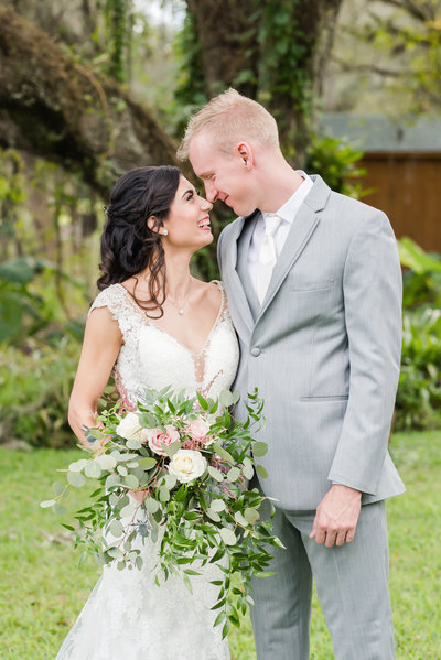 Bride and groom embrace and smile looking at each other nose to nose while holding free falling bouquet