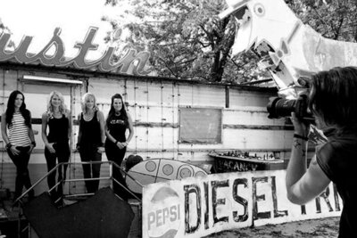 BTS photo band photography four members of female music group The Mrs standing against old building with Austin sign above it while Mark takes their photo black and white image