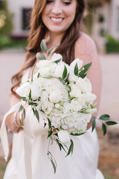 Bride holding all white bouquet bridal details