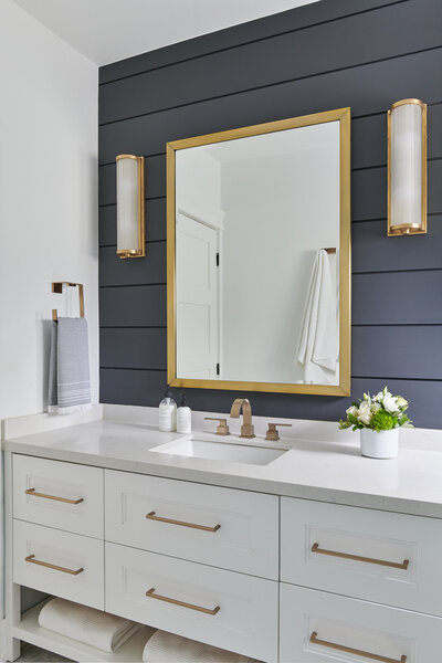 luxurious custom bathroom with white vanity, dark grey shiplap wall detail, and gold fixtures