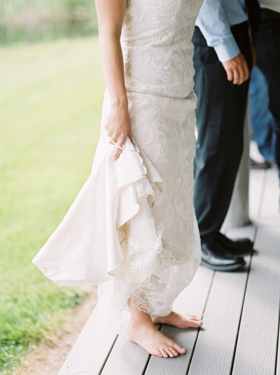 barefoot bride holding up wedding dress