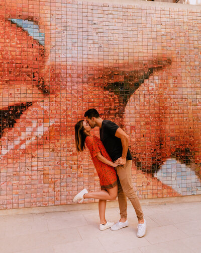 couple kissing in front of mosaic wall