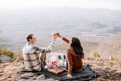 man and woman sitting on ground clinking glasses with chick fil a picnic