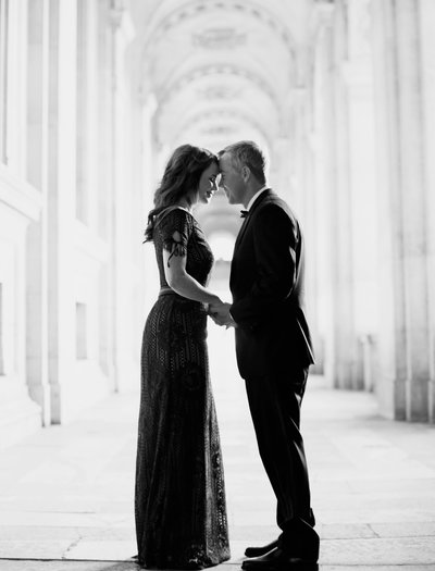 Couple stand forehead to forehead under arched walkway in Paris