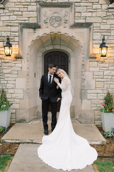 Bride and groom pose in front of Venue3Two mansion at their grand rapids wedding photo by Grand Rapids wedding photographer Cynthia Boyle