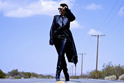 Portrait of Female Musician Leslie Cours Mather walking down road in long coat hand to sunglasses she wears telephone poles behind her