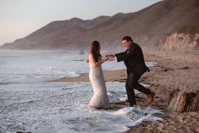 Wedding couple gets hit by wave on Big Sur California beach