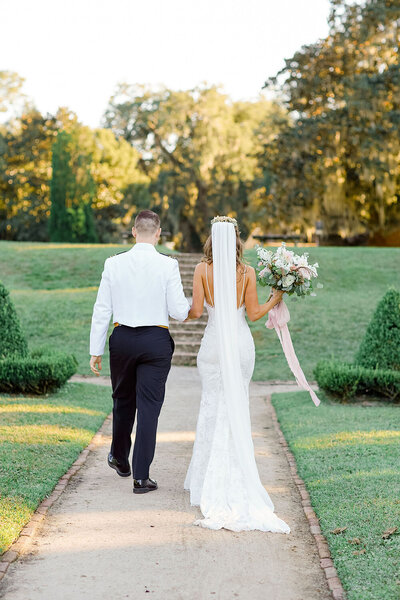 Fitted spaghetti strap bridal gown from Grace Loves Lace and military formal wear during a garden wedding recessional