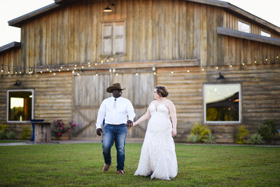 Bride and groom walk in front of barn at The Camellia Barn in MIssissippi