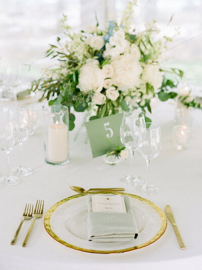 Reception place-setting with wine glasses, candles, gold cutlery, gold rimmed plate, and large white and green bouquet in the background