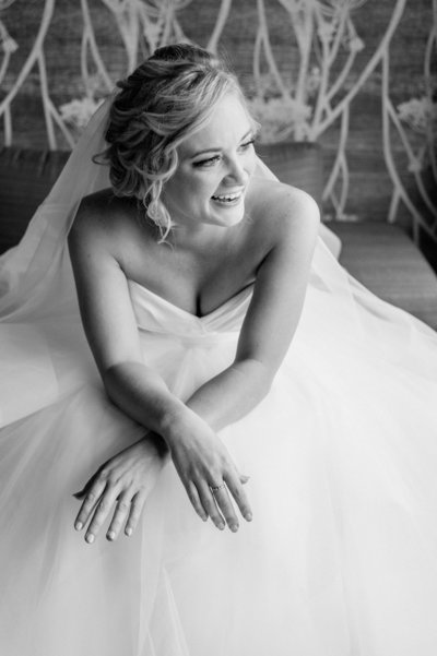 bride sitting on couch looking away and laughing