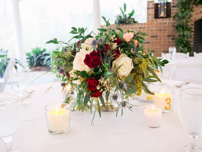 Burgandy and white table flowers with candles at The Mackey House Savannah GA