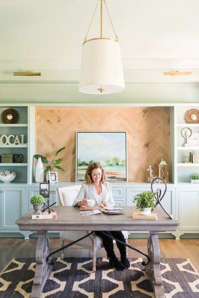 Nashville realtor sitting at her desk with a white coffee mug in her wood and seafoam office