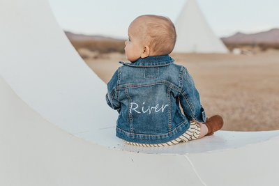 baby wearing embroidered denim jacket