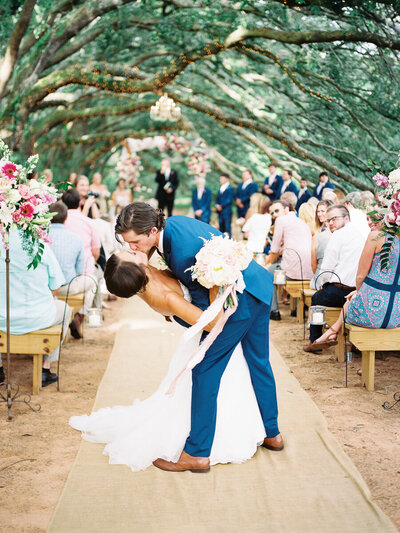 Destination wedding ceremony beneath Spanish moss and arching trees with the bride and groom in a blue suit dipping for a dramatic kiss at the end of the aisle with ribbons flowing from the bouquet in the wind.