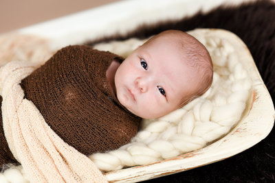 Beautiful Mississippi Newborn Photography: alert newborn boy wrapped in brown laying in dough bowl