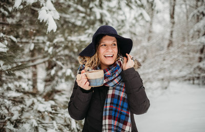 woman holds hat and laughs during snowstorm