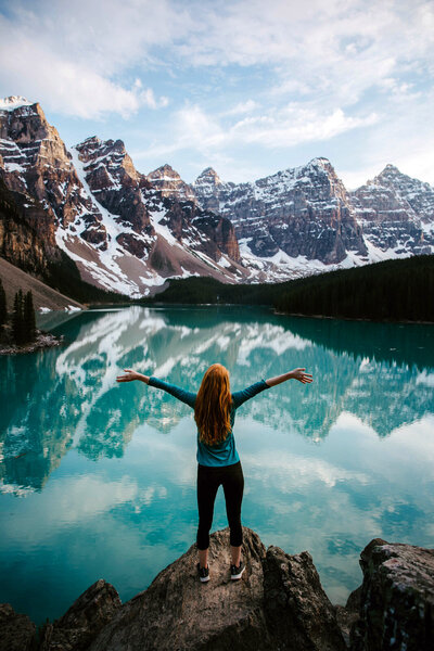 woman standing on rock in front of blue lake with mountains in background