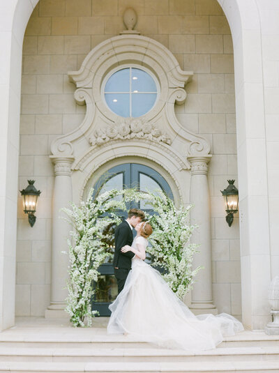 luxury couple kissing under arch outside of the olana