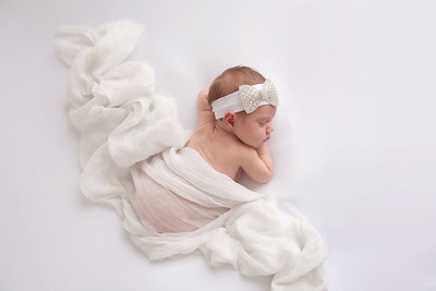 newborn baby girl on white background with white blanket and bow-1