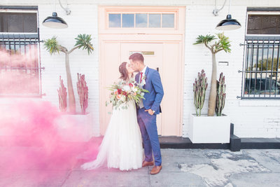 Bride and groom kiss on their wedding day holding beautiful bouquet as puff of pink smoke blows in from side