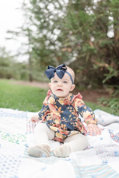 a sweet baby girl is sitting up on a quilt for family portraits in Brentwood Tennessee