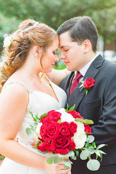 Bride with hair in French braid touching foreheads with groom wearing red rose boutonnière. Bride holding white and rose rose bouquet. Wedding in Northern Virginia captured by Ashley Eagleson Photography.