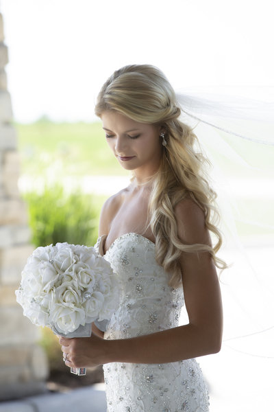 Bride with long blond hair and flowing veil looks at her bouquet