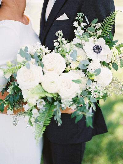 bride holds her white and greenery bouquet by LB Floristry at her August wedding, photography by Grand Rapids wedding photographer Cynthia Boyle