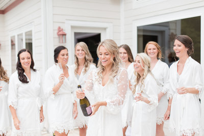 bride popping champagne with bridesmaids wedding morning by costola photography