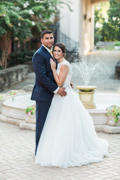 Brunette woman in wedding gown with groom posing in front of fountain