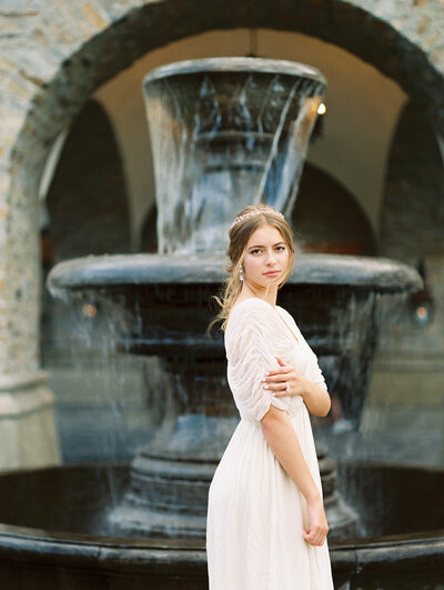 Bride standing in front of fountain looking over shoulder at camera