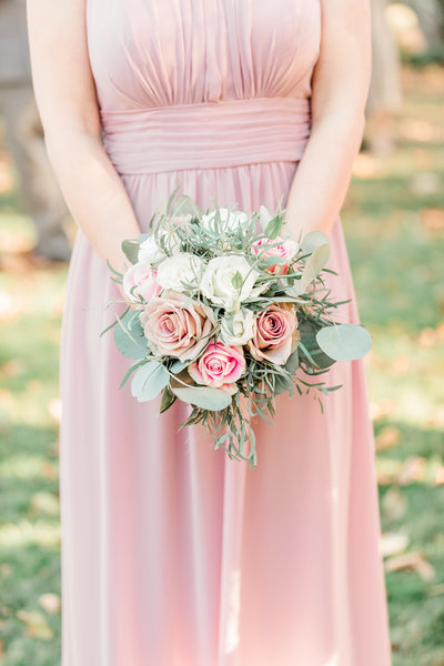 Detail show showing a bridesmaid in a pink dress holding bouquet.