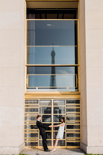 Bride and groom snuggle with the Eiffel Tower reflected in the glass, Paris, France, Destination Wedding Photographer