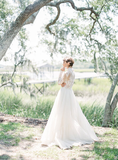 Bride standing in the sunlight beneath oak trees. Photographed by Amy Mulder PHotography.