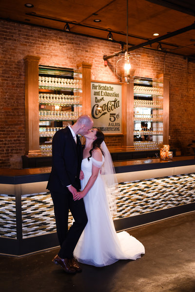 Couple kisses at The Bottling Company Hattiesburg MS Wedding