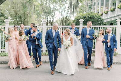 Bride and Groom walk with wedding party in Charleston