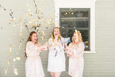 bride and bridesmaids popping confetti in matching robes